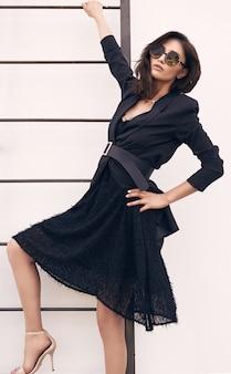 De schitterende heldere donkerbruine vrouw in manierkleding beklimt op de treden