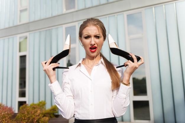 De schoenen van de bedrijfsdameholding in haar handen. triest jong meisje is niet blij met het dragen van hakken