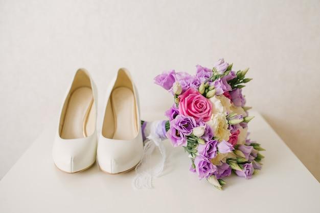 De schoenen van de bruid en het roze lila bruidsboeket liggen naast de witte achtergrond, de accessoires van de bruid