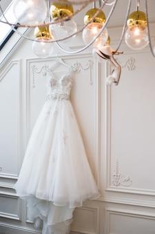 De schoenen van de bruid hangen aan de kroonluchter in het interieur van een luxehotel