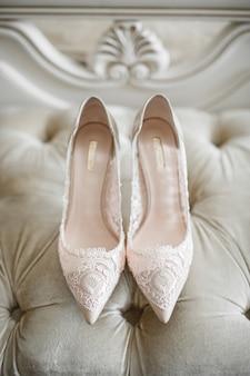 De schoenen van de bruid met kant bevinden zich op witte bank