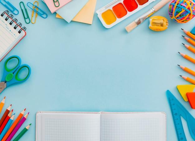 De school levert kantoorbehoeften op blauw, terug naar schoolconcept met exemplaarruimte voor tekst