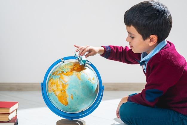 De schooljongen in een trui zit in een pose op de grond en speelt met een vliegtuig en een wereldbol