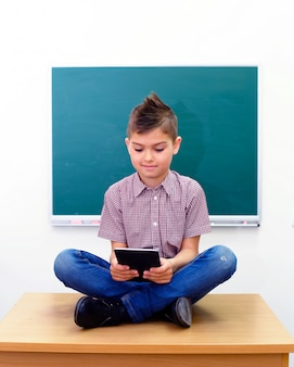 De schooljongen in lotusbloem stelt het bekijken tabletcomputer