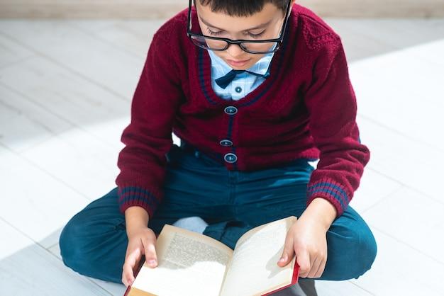 De schooljongen in trui en bril zit in lotushouding op de grond en bladert door een boek