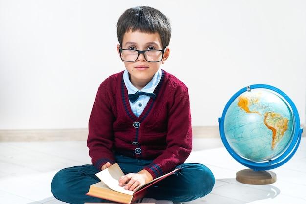 De schooljongen in trui en bril zit op de grond in lotushouding naast de wereldbol