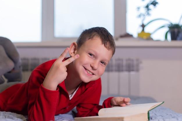 De schooljongen leest thuis een boek, afstandsonderwijs