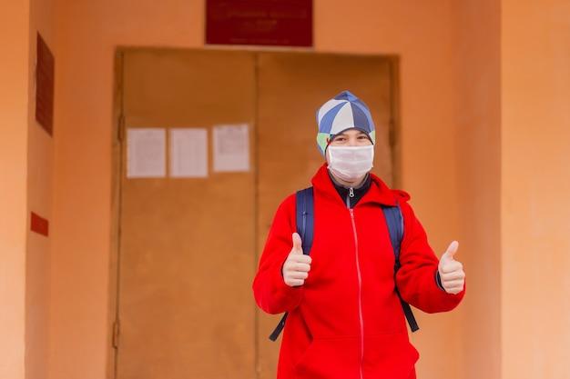 De schooljongen toont klas in beschermend masker