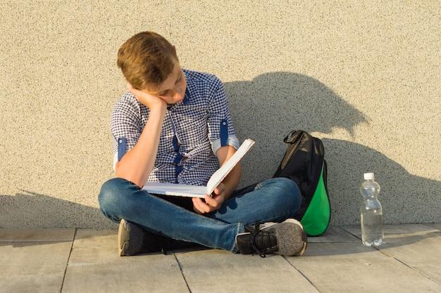 De schooljongen van de tiener leest handboek
