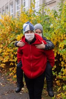De schoolkinderen in beschermende maskers op straat