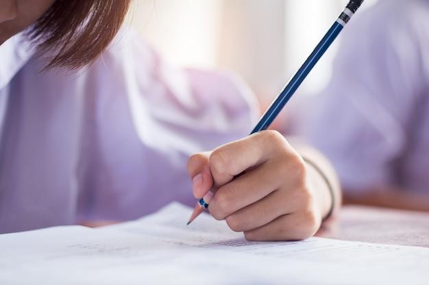 De schoolstudent neemt examen en schrijft antwoord in klaslokaal voor het concept van de onderwijstest.
