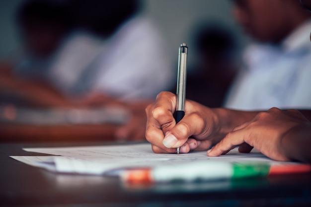 De schoolstudent neemt examen en schrijft antwoord in klaslokaal