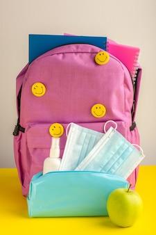De schooltas van het vooraanzichtkind met voorbeeldenboekennevel en maskers op geel bureau