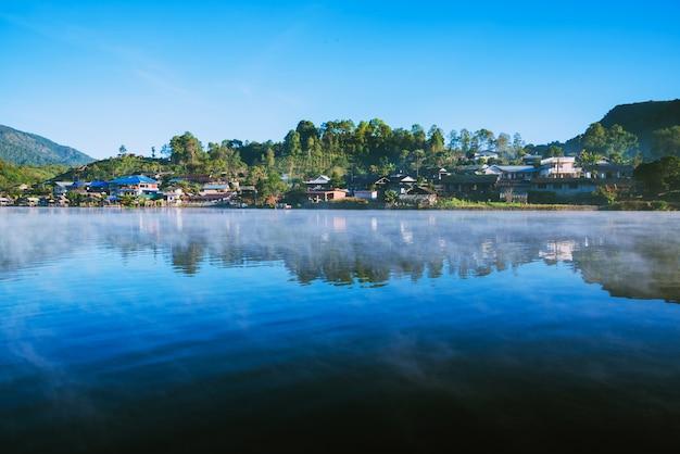 De schoonheid van de mist die 's ochtends van het oppervlak van het meer opsteeg in het dorp ban rak thai, in thailand.