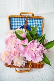 De schoonheid van een roze pioenrozenboeket in een vintage authentieke bruine koffer.