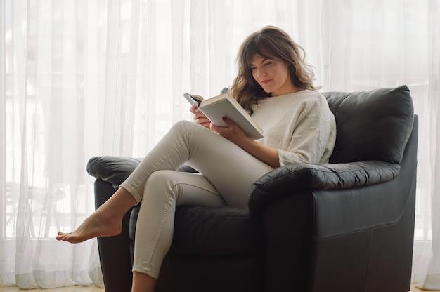 De schoonheids jonge vrouw leest thuis een boek