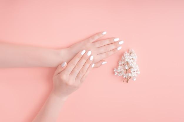 De schoonheidshanden van een vrouw met witte bloemen liggen op lijst, roze achtergrond. natuurlijke cosmetica en handverzorging, hydraterende en rimpelvermindering, huidverzorging