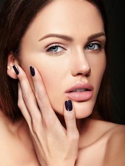 De schoonheidsportret van de glamourclose-up van mooi sensueel kaukasisch jong vrouwenmodel met naakte make-up wat betreft haar het perfecte schone huid stellen op donkere achtergrond