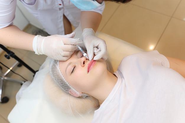 De schoonheidsspecialist maakt injecties van hyaluronzuur in het bovenste deel van de lip, waardoor het volume van de lippen van de cliënt toeneemt