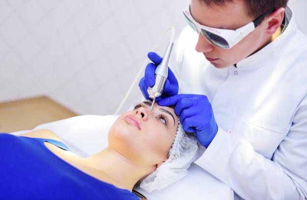 De schoonheidsspecialist verwijdert pigmentatie en vasculaire netten op de huid van de patiënt