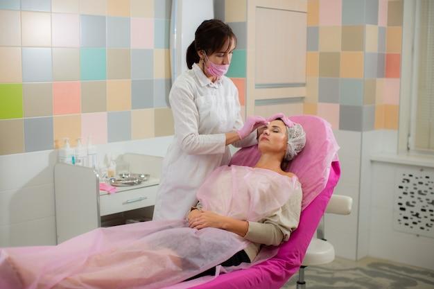 De schoonheidsspecialiste behandelt vóór de ingreep de huid van het gezicht van zijn patiënt.