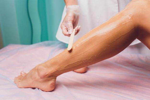 De schoonheidsspecialiste bereidt zich voor op het ontharen en brengt de crème met waxstick aan op de mooie vrouwelijke benen. schoonheidssalon.