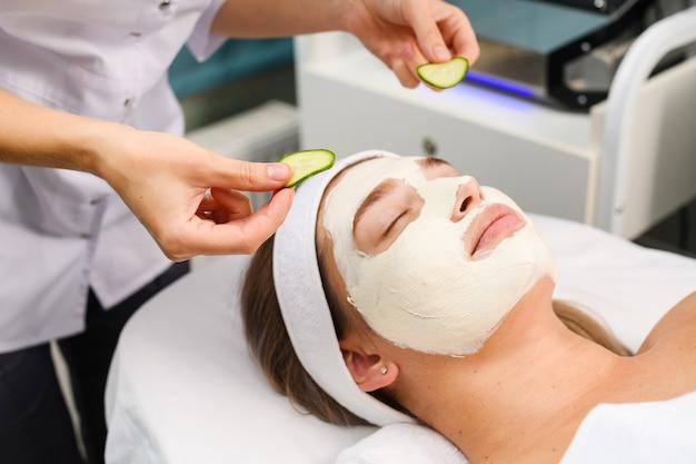De schoonheidsspecialiste brengt een natuurlijk wit vochtinbrengend gezichtsmasker aan en verfrist de ogen met komkommer