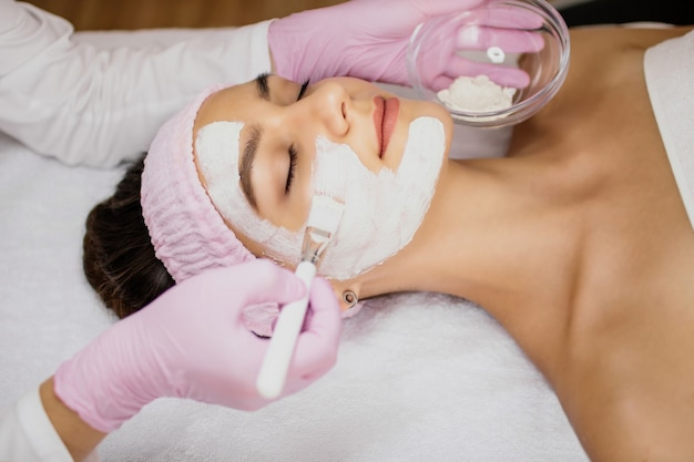 De schoonheidsspecialiste brengt met een wit penseel een masker van witte klei aan op het gezicht van het meisje