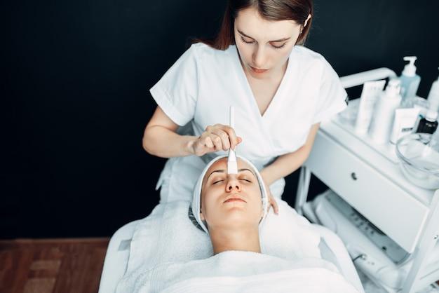 De schoonheidsspecialiste maakt de verjongingsprocedure aan de patiënt