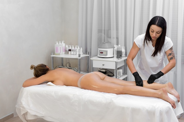 De schoonheidsspecialiste van het jonge meisje masseert een vrouw, ze wrijft haar benen in met olie. anticellulitis massage in de spa salon.