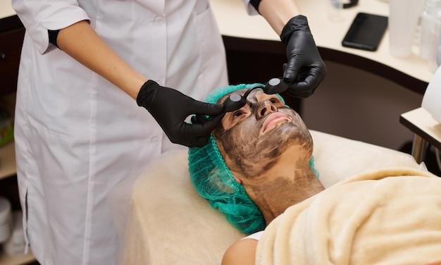 De schoonheidsspecialiste zet vóór de ingreep een zwarte veiligheidsbril op de patiënt