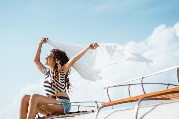 De schoonheidsvrouw geniet van slagwind met golvende witte sjaal