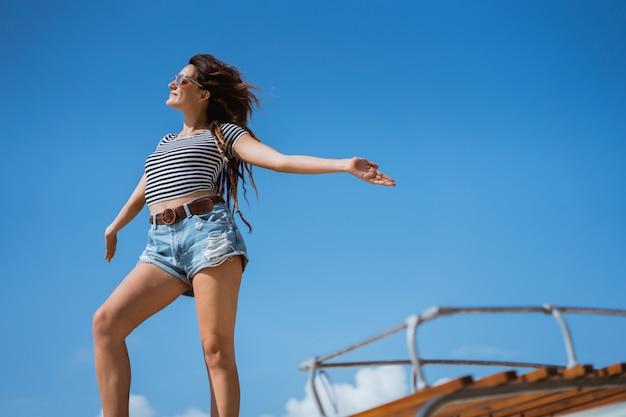 De schoonheidsvrouw status geniet van slagwind op het dak