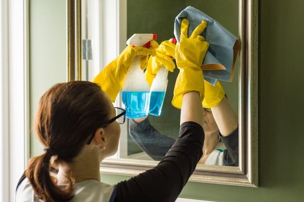 De schoonmakende dienst, vrouw maakt thuis spiegel in badkamers schoon