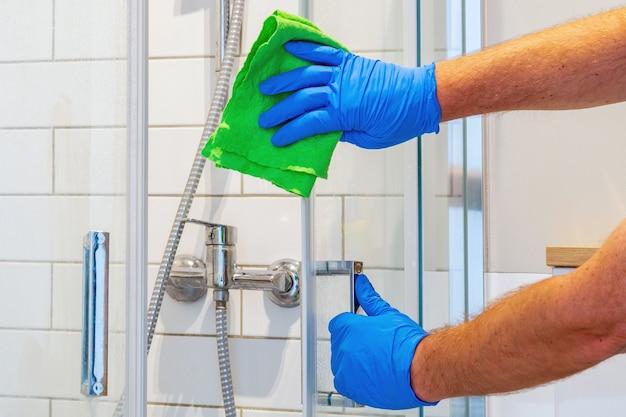 De schoonmaker wast de douchedeur in de badkamer met wasmiddelen. idee voor het schoonmaken van de badkamer