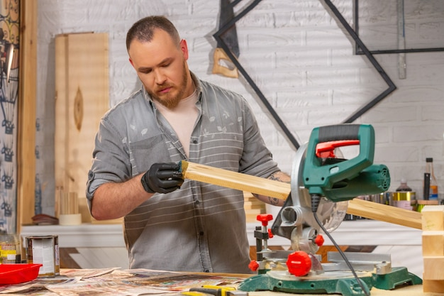 De schrijnwerker bedekt het houten deel in de werkplaats