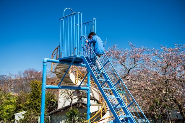 De schuif van het jongensspel in de lentepark, matsumoto