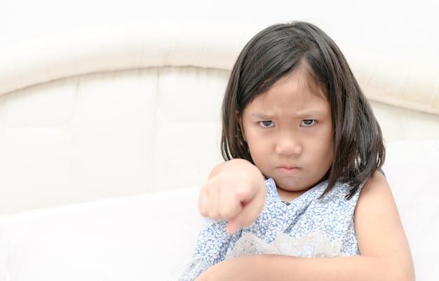 De schuld, beschuldiging. portret boos meisje wijzende vinger naar iemand ontevreden op bed. negatief mens