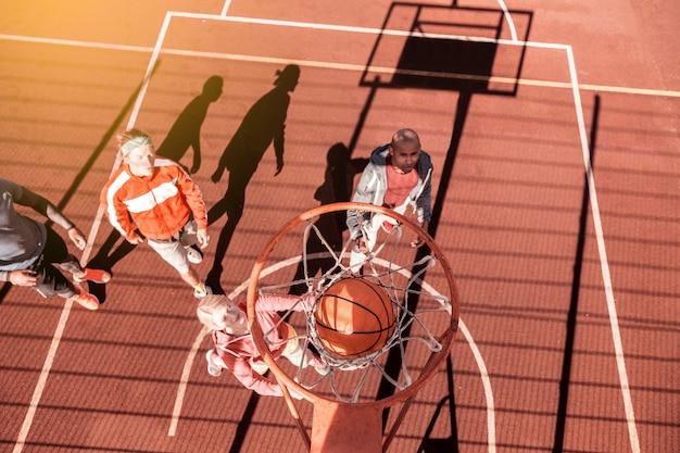 De score. bovenaanzicht van een oranje bal die door de basket gaat tijdens het scoren van het doel