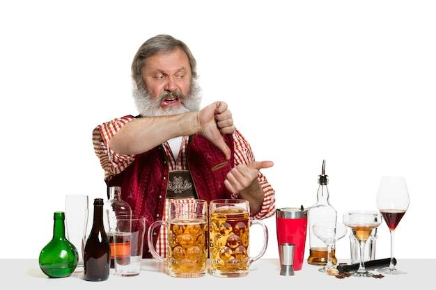 De senior deskundige mannelijke barman met bier in de studio op wit wordt geïsoleerd