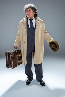 De senior man als detective of baas van maffia op grijze studio achtergrond