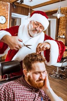 De senior man in kerstman kostuum werkt als persoonlijke meester met een schaar bij de kapper voor kerstmis