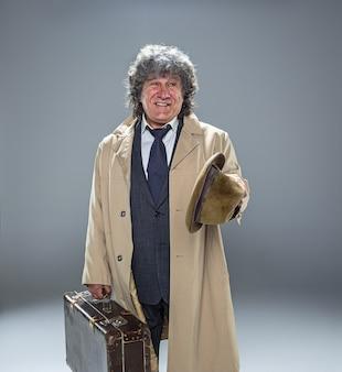 De senior man in mantel als detective of maffiabaas. studio die op grijs in retro stijl is ontsproten. oudere man met hoed en koffer