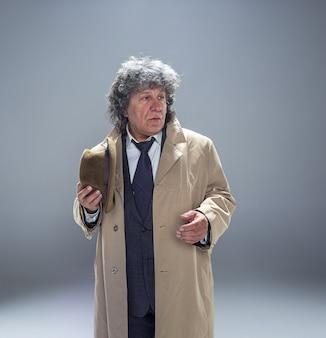 De senior man in mantel als detective of maffiabaas.