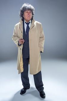 De senior man in mantel met sigaar als detective of maffiabaas. studio die op grijs in retro stijl is ontsproten