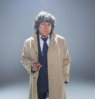 De senior man in mantel met sigaar als detective of maffiabaas.