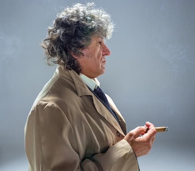 De senior man met sigaar als detective of baas van de maffia