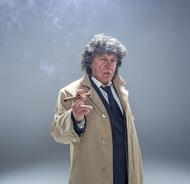 De senior man met sigaar als detective of baas van maffia op grijs