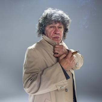 De senior man met sigaar als detective of baas van maffia op grijze studio achtergrond