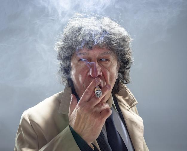 De senior man met sigaar als detective of baas van maffia op grijze studio ruimte